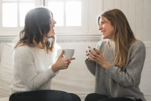 Two women having a conversation with coffee