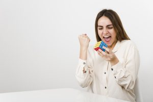 Woman playing with the Rubik's Cube. Rubik's cube invented by a Hungarian architect Erno Rubik in 1974.