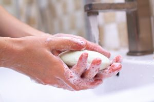 Hand hygiene. Person in the bathroom is cleaning and washing hands with soap