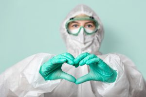 Medical worker in safety glasses, mask and suit makes a heart sign