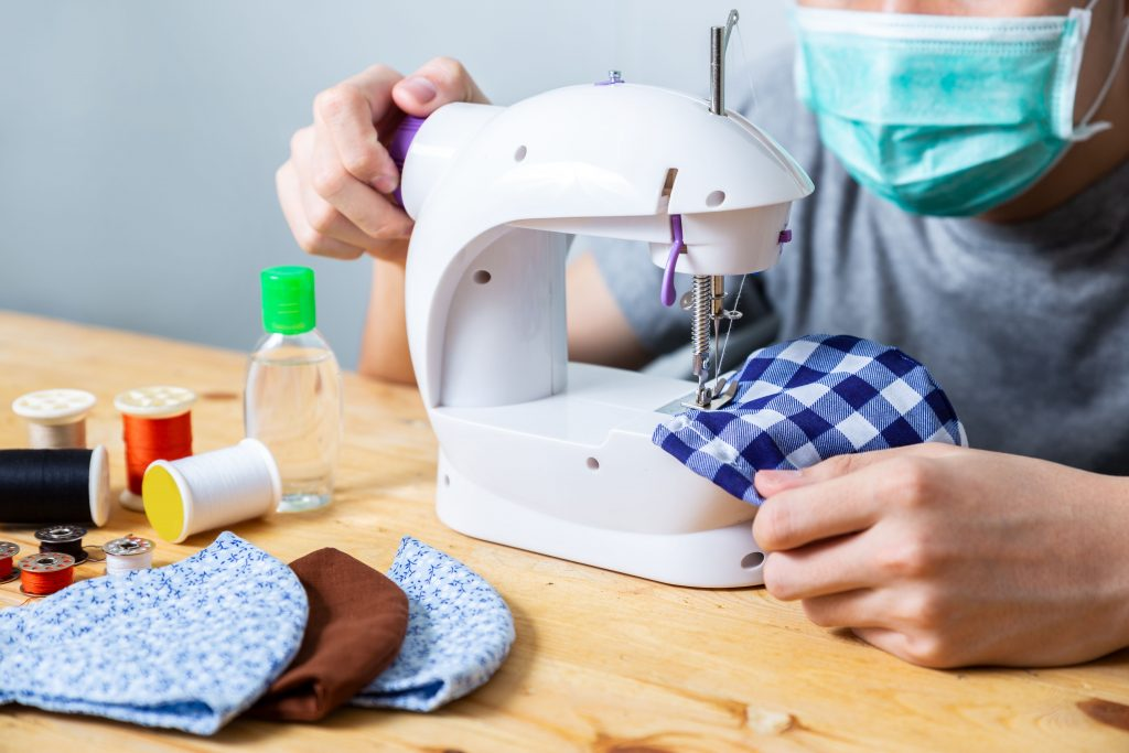 Woman sewing cloth cotton face mask to protect against the corona virus at home. Homemade handicraft protective mask against covid 19 virus. Reusable face mask.